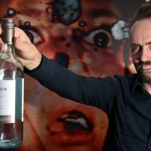 Transmedia artist Simon Wilkinson, of England, offers a bottle outside his virtual reality...