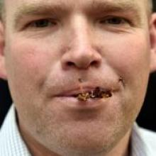 Otago Daily Times reporter Shawn McAvinue eats a locust in Dunedin yesterday.