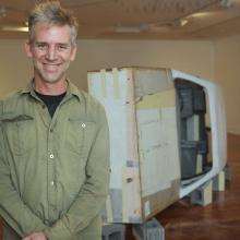Glen Hayward and his life-sized replica of a 1980's Toyota Corolla at Dunedin Public Art Gallery....