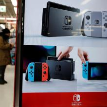 Monitor showing Nintendo Switch game consoles is seen at an electronics store in Tokyo. Photo:...