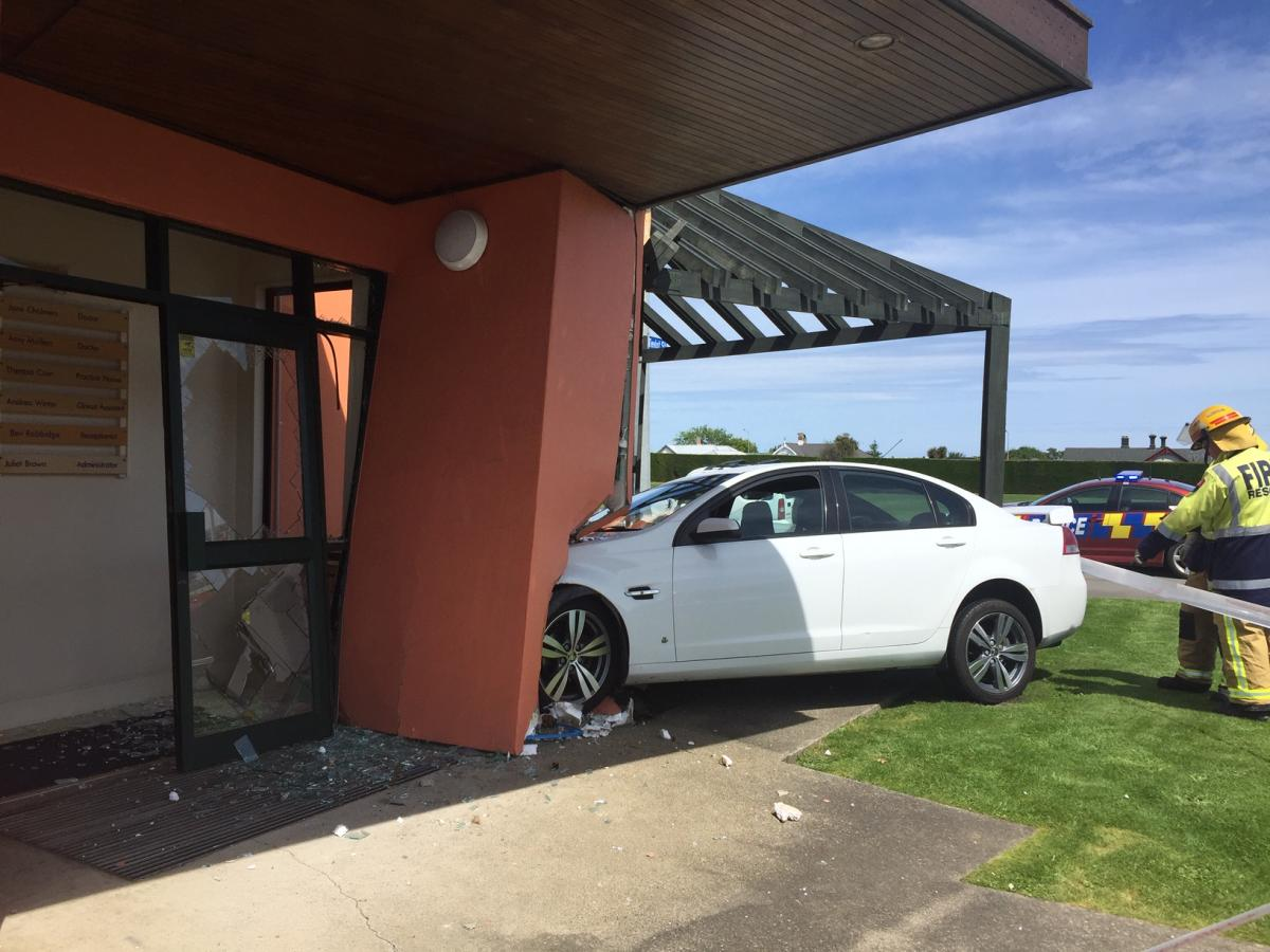 Car hits building after two vehicles collide