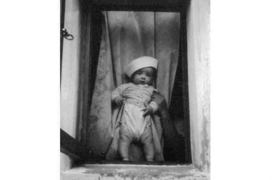 Wearing a sailor hat, baby Earl is framed by the lounge window. Photo supplied.