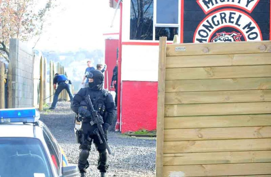 An Armed Offenders Squad member stands guard outside the former Mongrel Mob Aotearoa headquarters.
