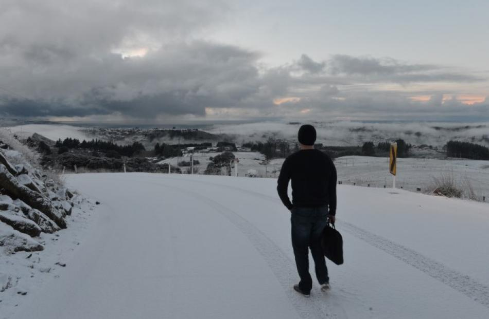 A man walks to work in Dunedin after ditching his car this morning. Photo Stephen Jaquiery