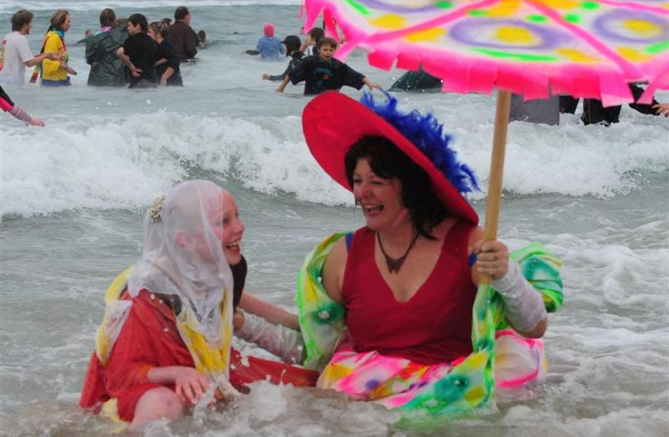 Amber Smith (11) and Linda McKie sit in the surf.