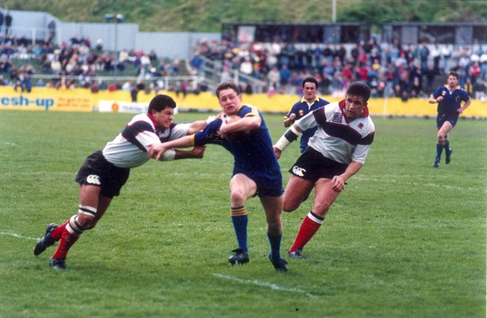 Otago winger Marc Ellis fends off a North Harbour player on the way to the tryline at Carisbrook...