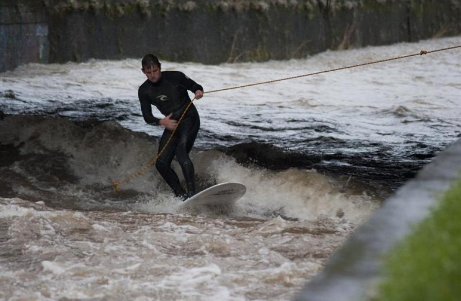 Surfers ride the current on the swollen Leith yesterday afternoon. Photo by Max Bellamy.