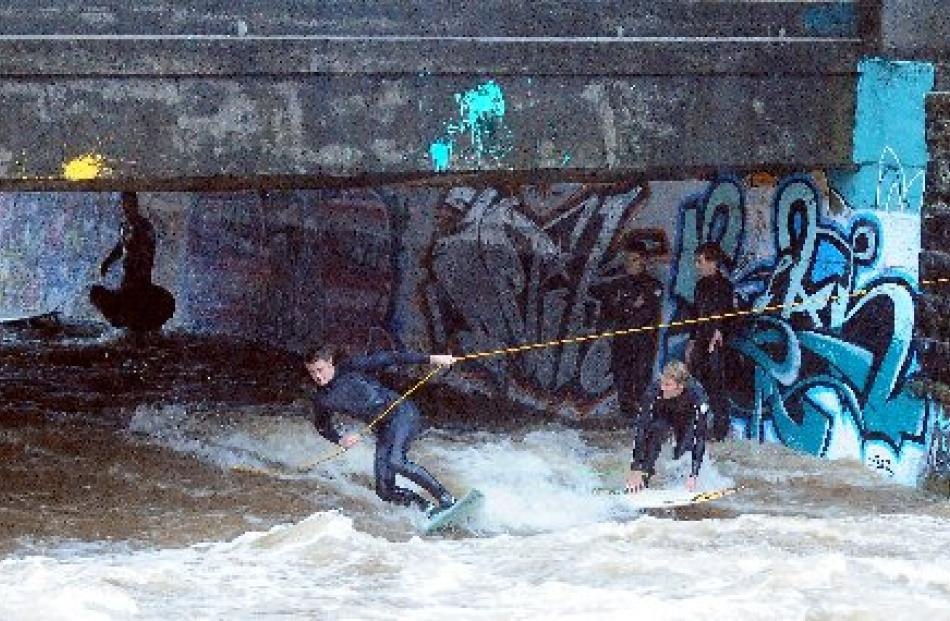 Surfers ride the current on the swollen Leith yesterday afternoon. Photo by Craig Baxter.