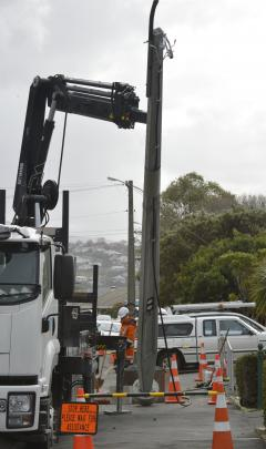Contractors replace a power pole in Forbury Rd, which was felled by high winds last week. Photo:...