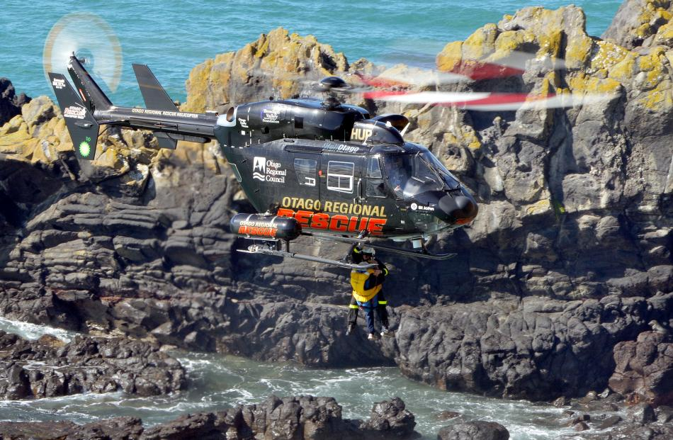 A rescue helicopter hovers above the rocks.