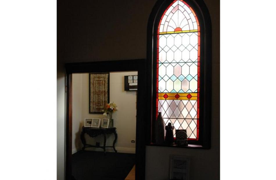 Looking from the original church space lit by leadlight windows into the entrance way.