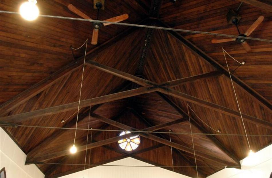 The tongue and groove church  ceiling with a small rose window at the gable.