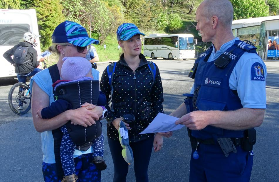 Sergeant Chris Brooks hands posters to Australian visitors Emma Potter, with Kirby (10 months)...