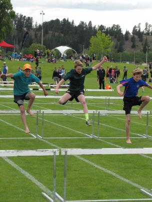 Julian Gerritsen (11, left), of Goldfields Primary School in Cromwell, Caleb Kitto (11), of Roxburgh Primary, and Finley Davies (11), of Arrowtown School, clear all obstacles in the under-12 hurdles.