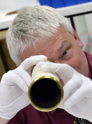 Otago Museum director Dr Ian Griffin inspects the museum's 1736 telescope in Dunedin yesterday....