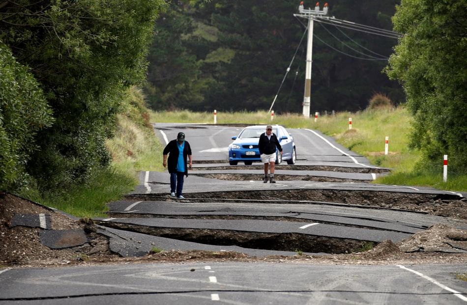 Local residents Chris and Viv Young look at damage caused by an earthquake along State Highway...