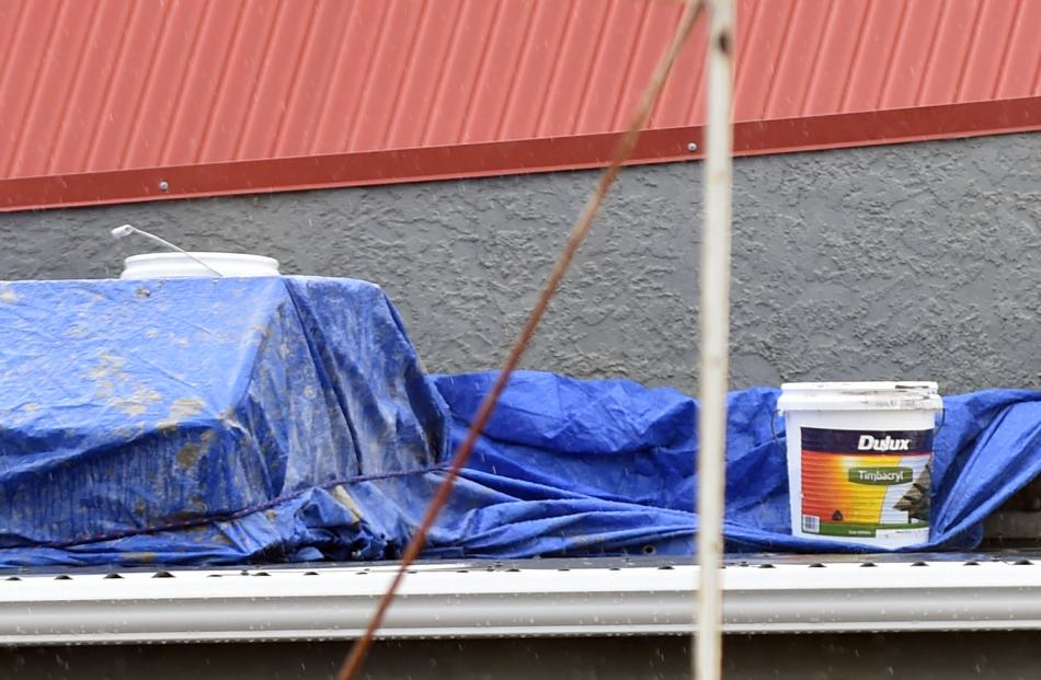 Paint cans are used to hold down a tarpaulin on top of a leaky Aurora Energy substation in...