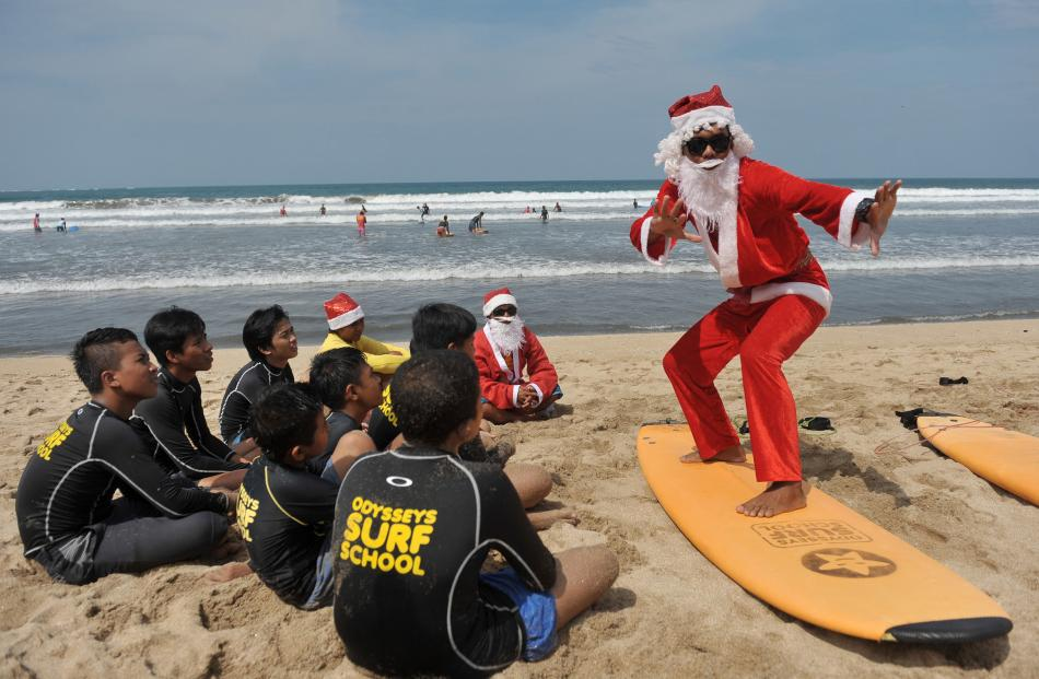 A surfing instructor dressed as Santa gives a lesson to orphans on Kuta Beach in Bali. Photo:...