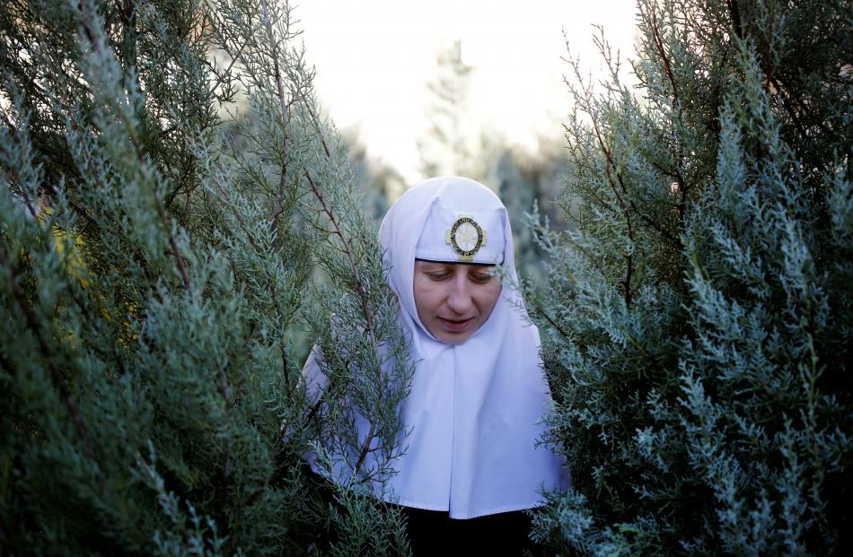 A nun with Christmas trees, handed out annually by the municipality, in Jerusalem's Old City....