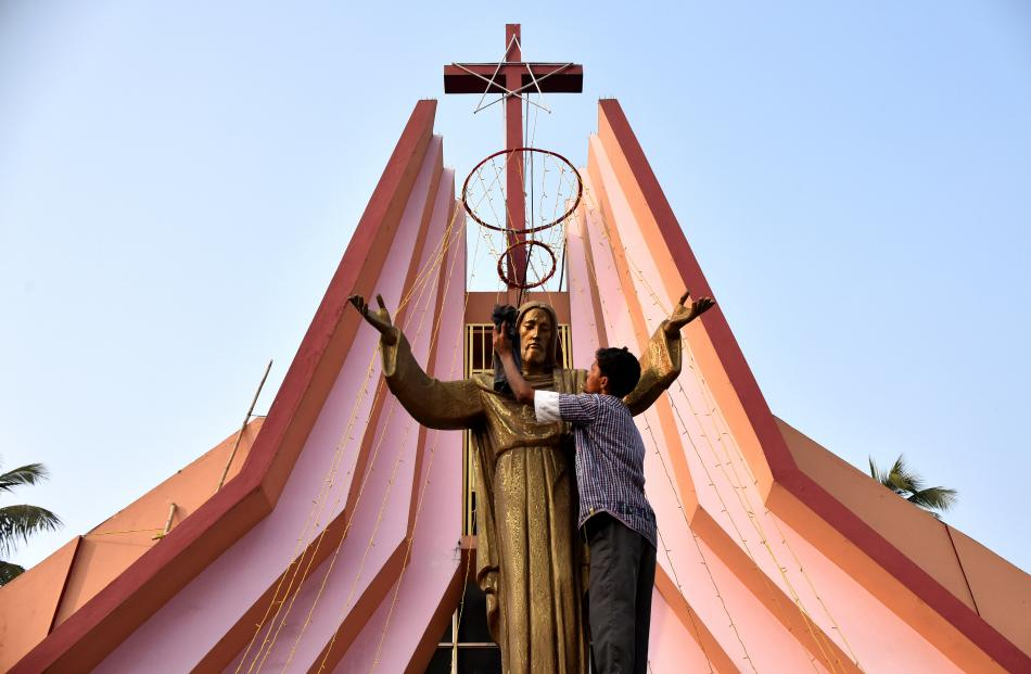 In India, a worker cleans a statue of Jesus Christ at a church in Guwahati. Photo: Reuters