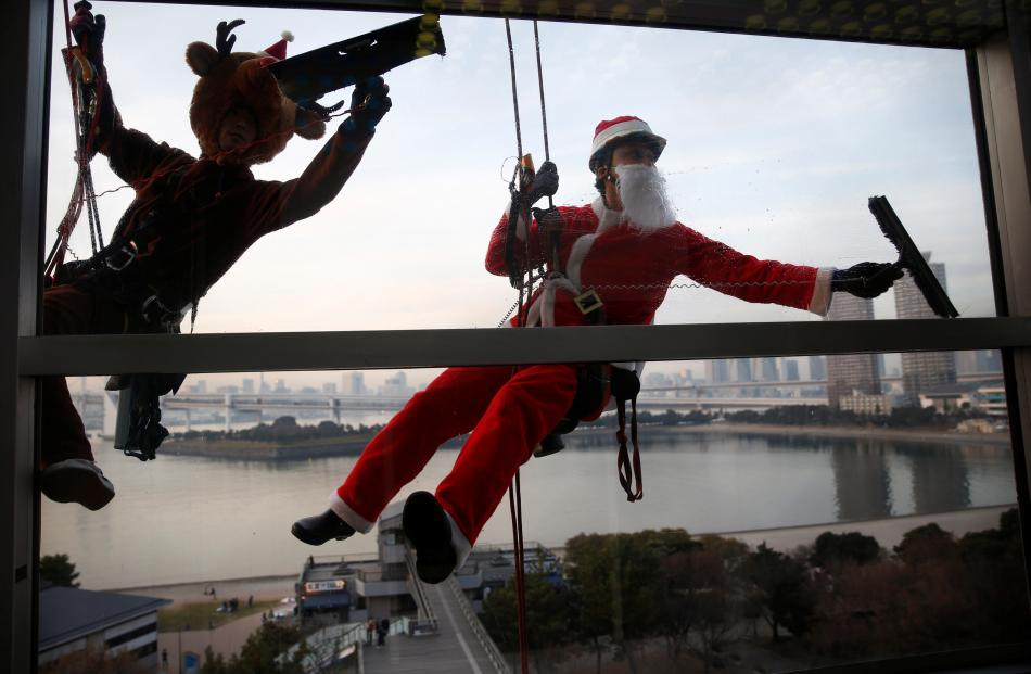 Window cleaners dressed as Santa Claus and a reindeer in Tokyo. Photo: Reuters