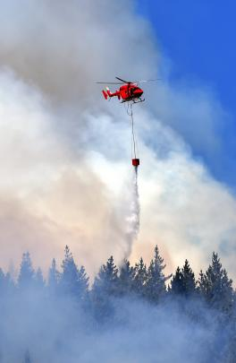 One of five helicopters to be deployed empties a moonson bucket on the fire. Photo by Peter McIntosh.