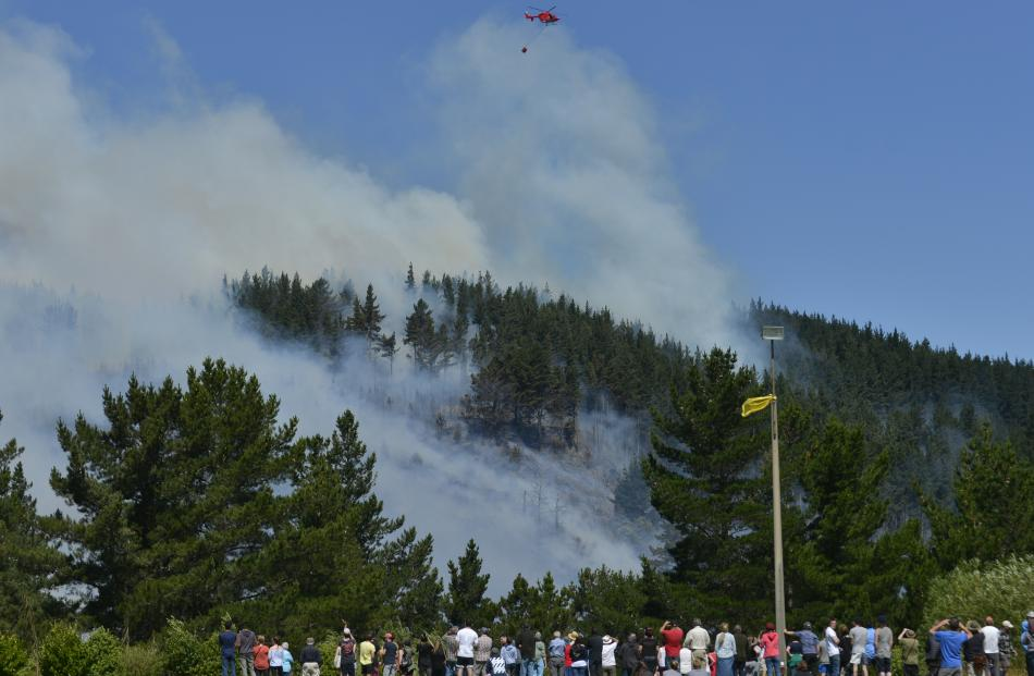 Onlookers at Opoho Park watch as a helicopter with a monsoon bucket operates above the fire on Signal Hill yesterday. Photo by Gerard O'Brien.