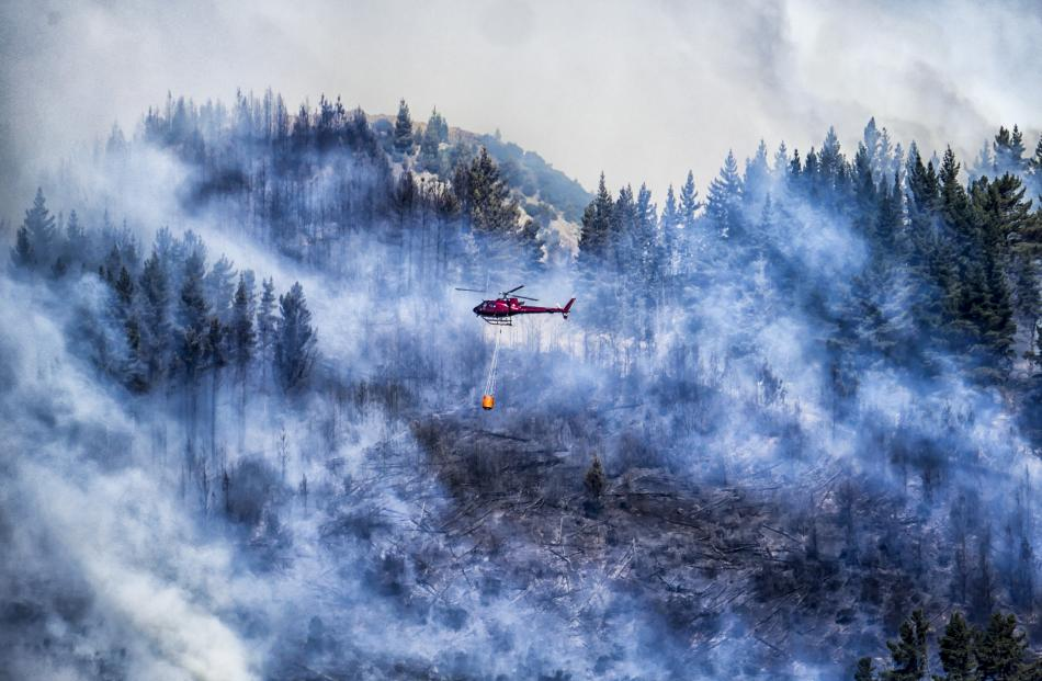 A helicopter with a monsoon bucket flies through the smoke fighting the fire at Signal Hill yesterday. Photo: Melissa Purnell
