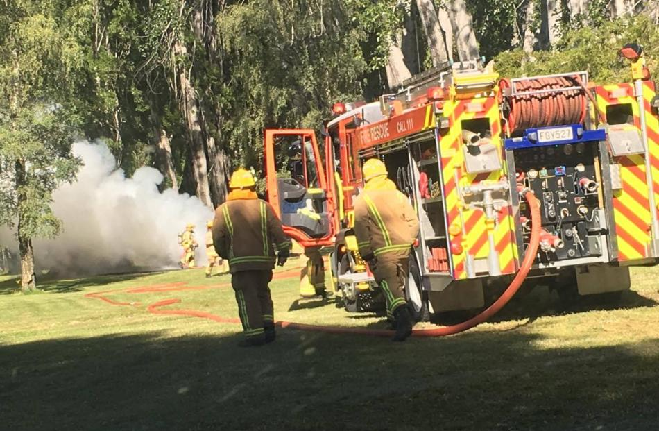 Firefighters rush to put out a van in flames at Pembroke Park in Wanaka. Photo: Ryan Murray