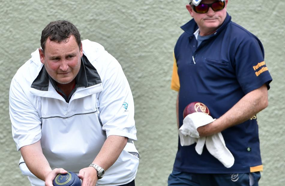 Graeme Hislop (left,  South Otago),  watched by Rodney Fleming (Forbury Park),  prepares to  play a bowl during the final of the Festival Fours in Dunedin yesterday. Hislop was a key figure in South Otago's win. Photos by Peter McIntosh.
