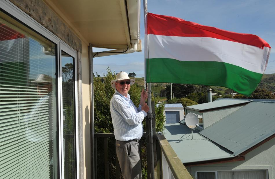Clark McLean lowers the flag of Hungary at his Harington Point house. Photos: Christine O'Connor.
