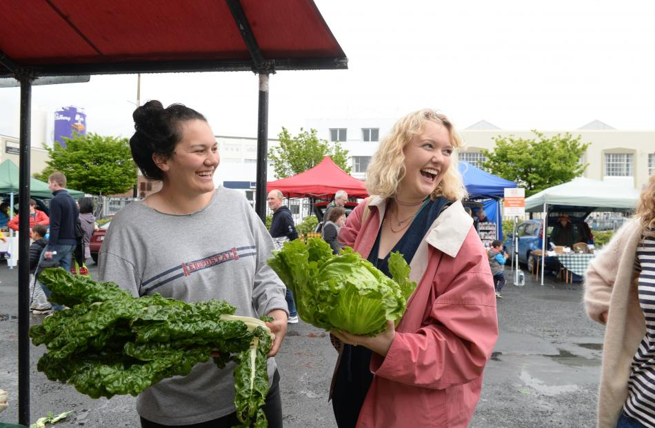 Students Karleigh O'Connor (22, left) and Emma Lunniss (23) check the vegetables at McArthurs Berry Farm Outram's stall at the Otago Farmers Market. Photos by Linda Robertson.