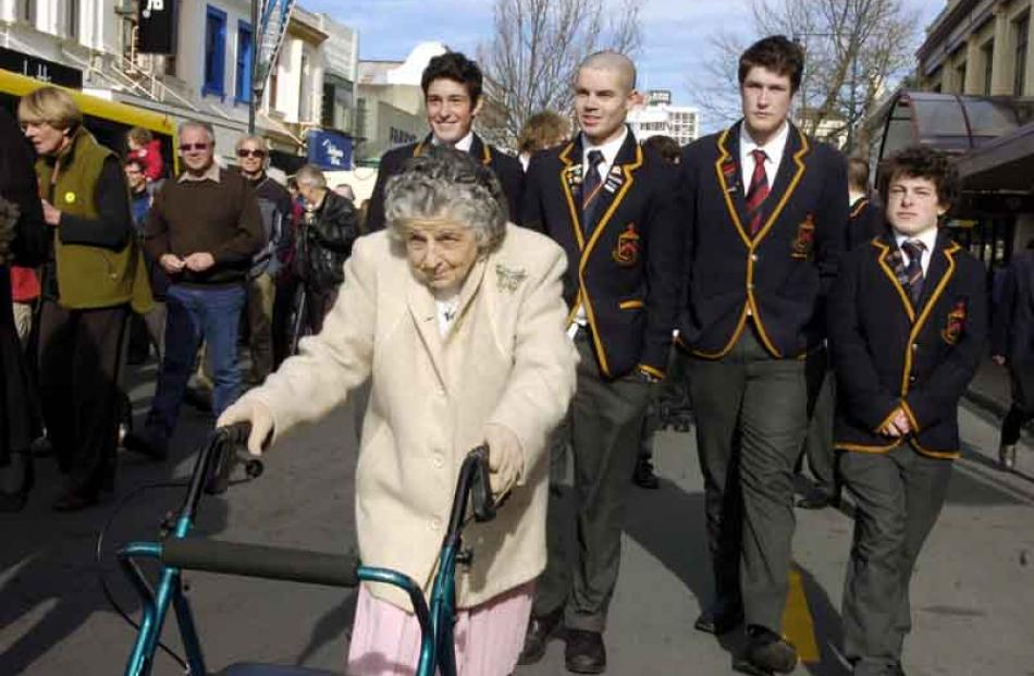 Mrs Norma Beardsmore (86) walks along George St surrounded by John McGlashan year 13 boys from...