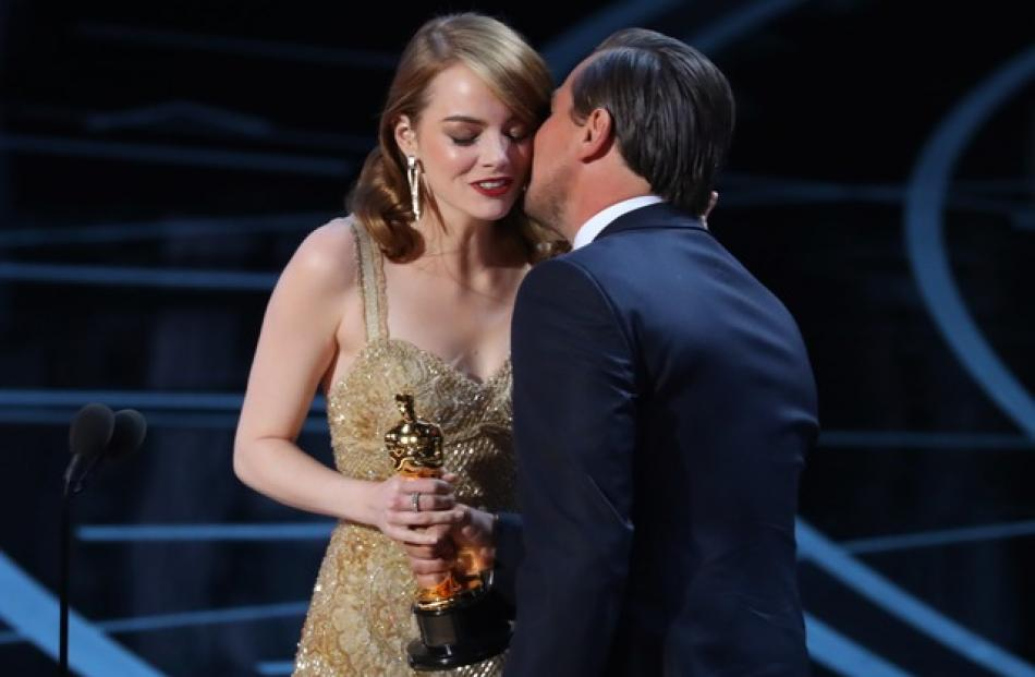 "Best Actress winner Emma Stone is congratulated by Leonardo DiCaprio as shes accept her award for ""La La Land.""Photo: Reuters"