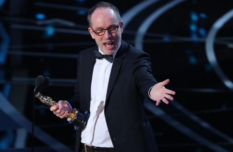 "Kiwi John Gilbert accepts the Oscar for Best Film Editing for ""Hacksaw Ridge"". Photo: Reuters"