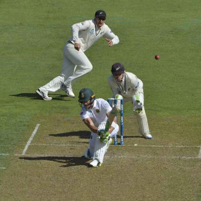 Du Plessis plays a sweep shot as Watling and Ross Taylor look on.