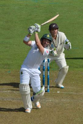 Elgar plays down the ground to the boundary as New Zealand wicketkeeper BJ Watling looks on.