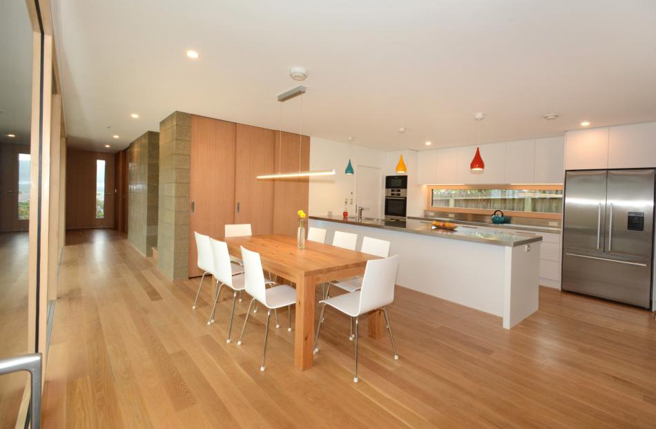 The sunlit hall leads from the front door past a block wall to the open-plan kitchen and dining...
