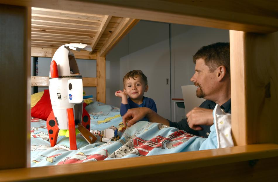John Crump plays on a bunk with son Micah (2). He and wife Jen wanted a healthy environment for...