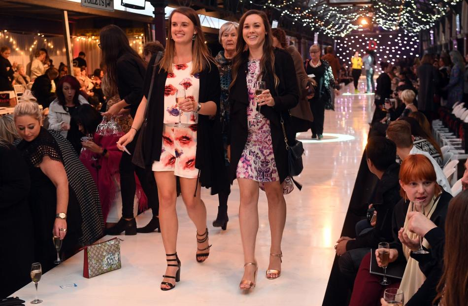 Ellyn Robertson (left) and Louise Anderson, both of Dunedin, head down the catwalk to their seats.