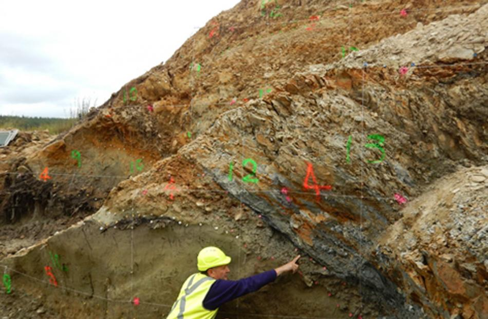 Prof Mark Stirling points at the Akatore Fault, near Dunedin. Photo: supplied.