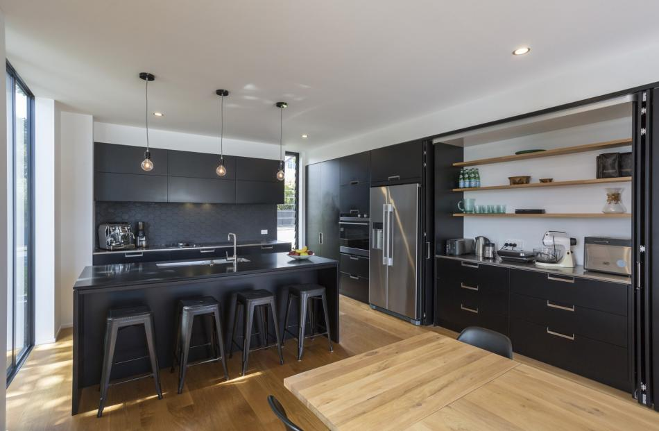 Matt and low-sheen finishes were used in the kitchen, which has gas and induction cook-tops. PHOTO: GRAHAM WARMAN
