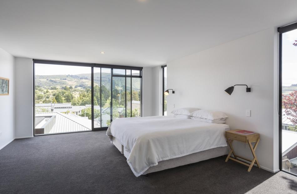 The master bedroom on the top floor has a glass stacking door with a half-height balustrade for safety. The owners never tire of the view out to Flagstaff. PHOTO: GRAHAM WARMAN