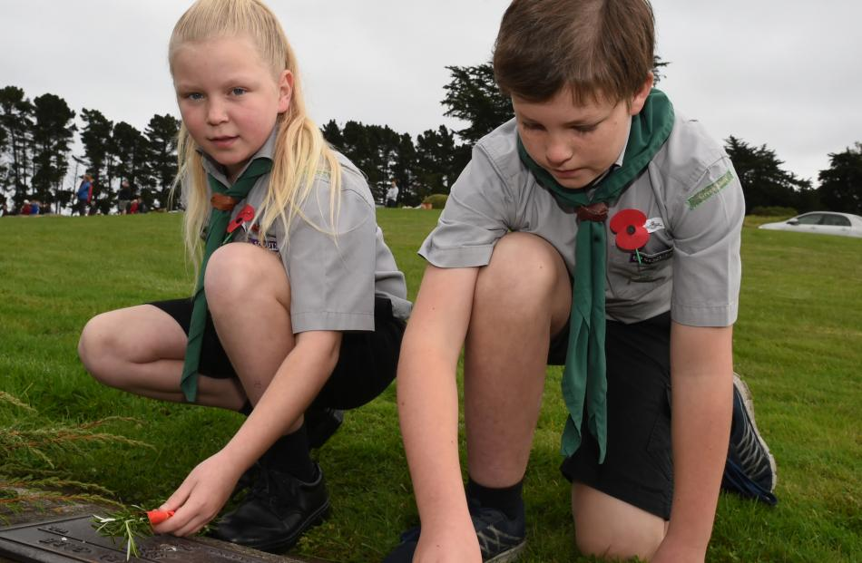 Green Island Scouts Alice Barrett (11) and Jonathan Tucker (10) lay posies of rosemary on the veterans graves at Green Park Cemetery, near Waldronville. Photo: Gregor Richardson.