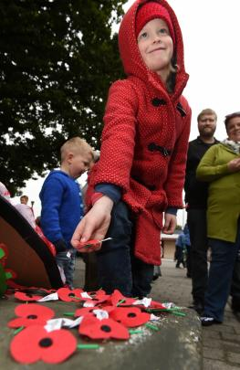 Gabby McGowan (7), of Mosgiel, lays a poppy at the foot of the Mosgiel cenotaph. Photo: Gregor Richardson.
