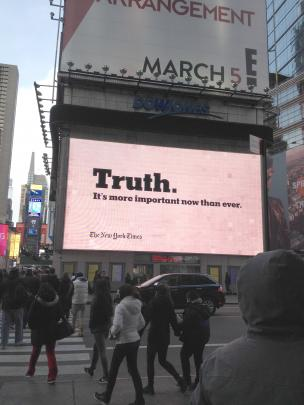 An electronic billboard in Times Square advertising The New York Times, reads: ''Truth. It's more...