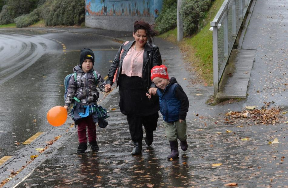 Kiri Smith walks her sons Te Mauri (7) and Rongomai (4) home along George St during a downpour in...