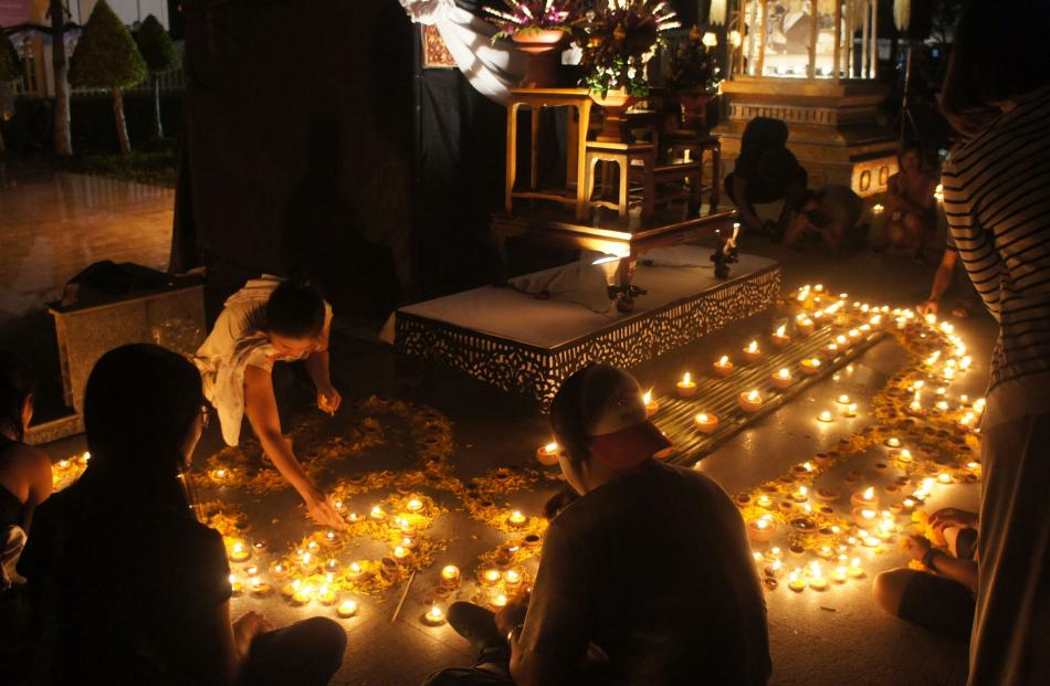 Families light candles in memory of Thailand's late King Bhumibol Adulyadej at Chiang Mai's Three...