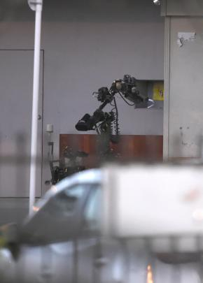 A robot operated by the squad inspects the package before it was destroyed. Photo: Gregor Richardson