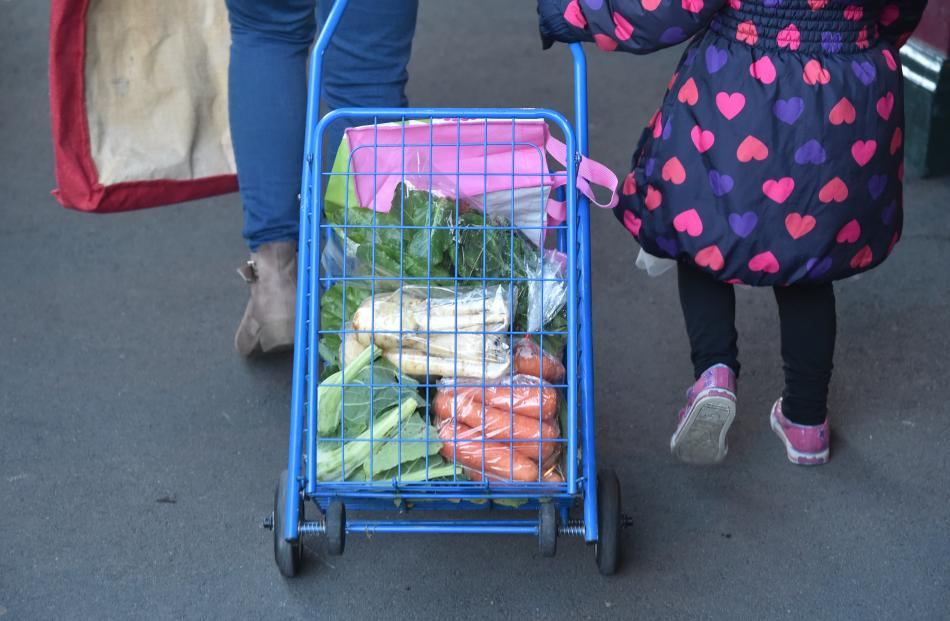 A visitor carries their purchases in a trolley.